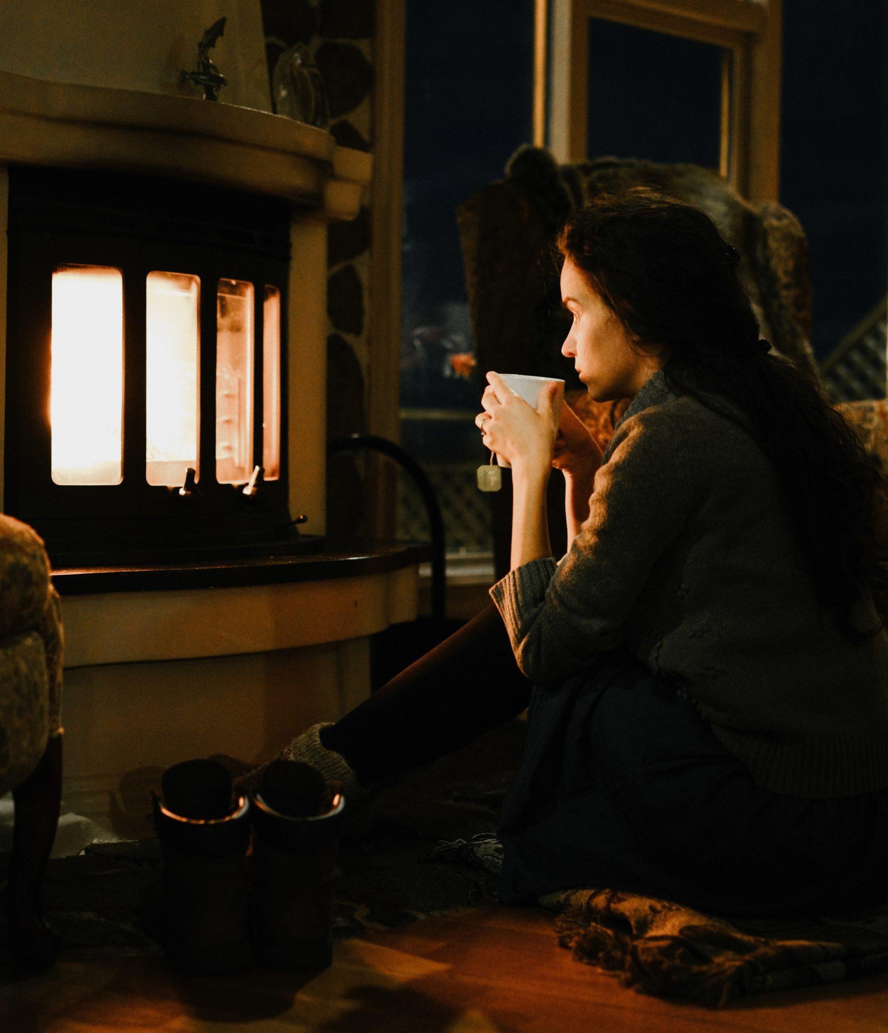 Jente med kopp foran peisen