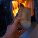 Hånd legger kubbe inn i peis